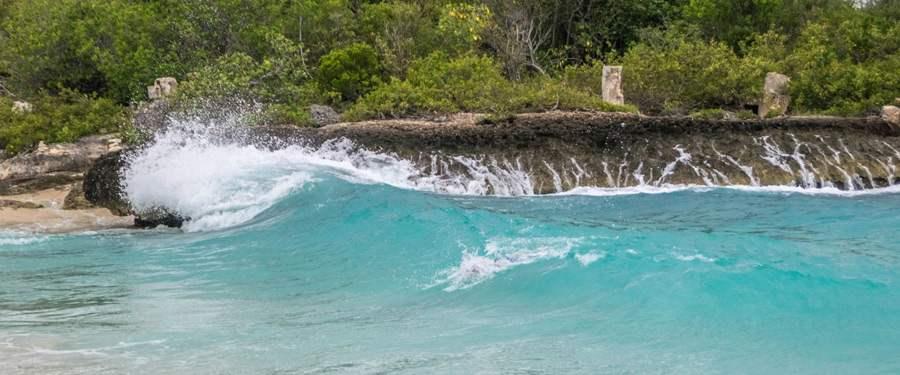 De rollende golven van Mullet Beach, het strand naast Maho beach.