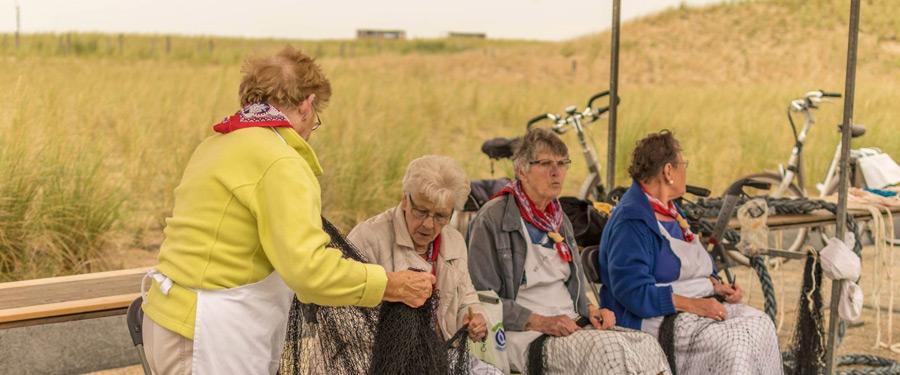 Enkele Katwijkse dames die bezig zijn met het herstellen van visnetten.