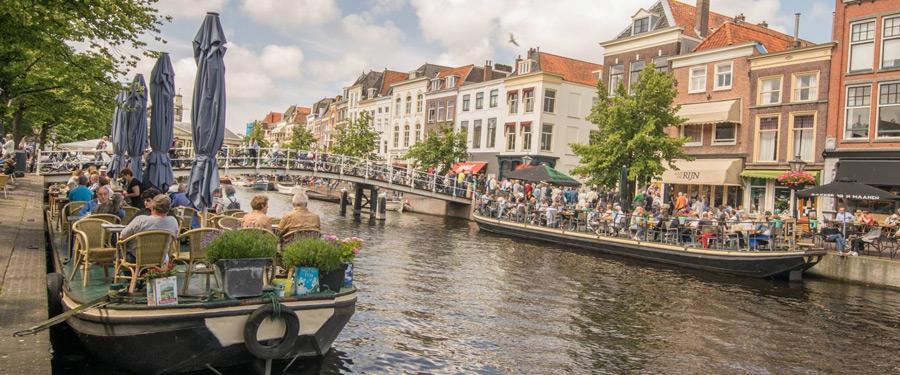 Genieten van de grachten in Leiden, terwijl je de bootjes voorbij ziet varen.