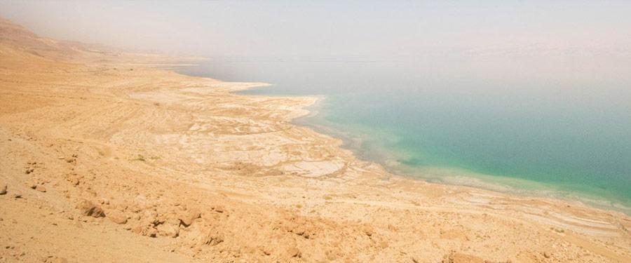 De dode zee strekt zich uit over Israel en Jordanië. Drijf op het zoute water en geniet van een kuur met het dode zee slijk!
