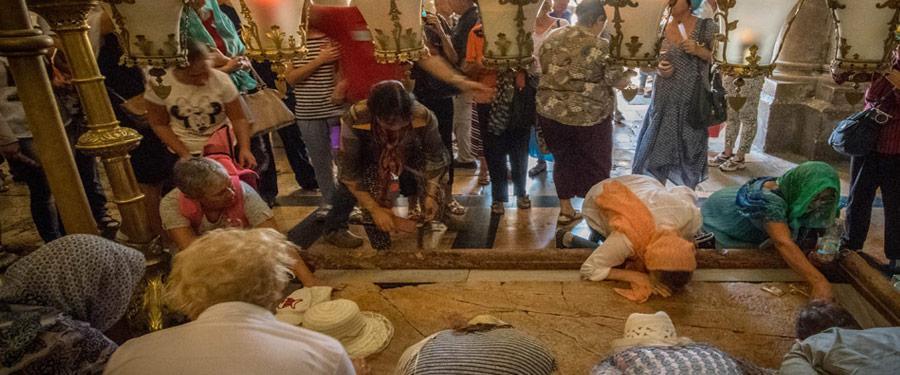 Een dagelijks tafereel binnenin de Heilige Grafkerk. Vrouwen knielen neer op de graftombe van Jezus.