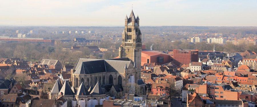 Uitzicht over Brugge met de Halletoren of het belfort prominent in beeld.