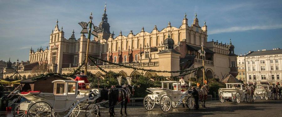 Sukiennice of de lakenhallen van Krakau met op de voorgrond enkele van de romantische koetsen die door Krakau trekken.