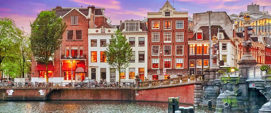 Enkele mooie rijtjeswoningen in Amsterdam. Op de voorgrond een van de ontelbare grachten.