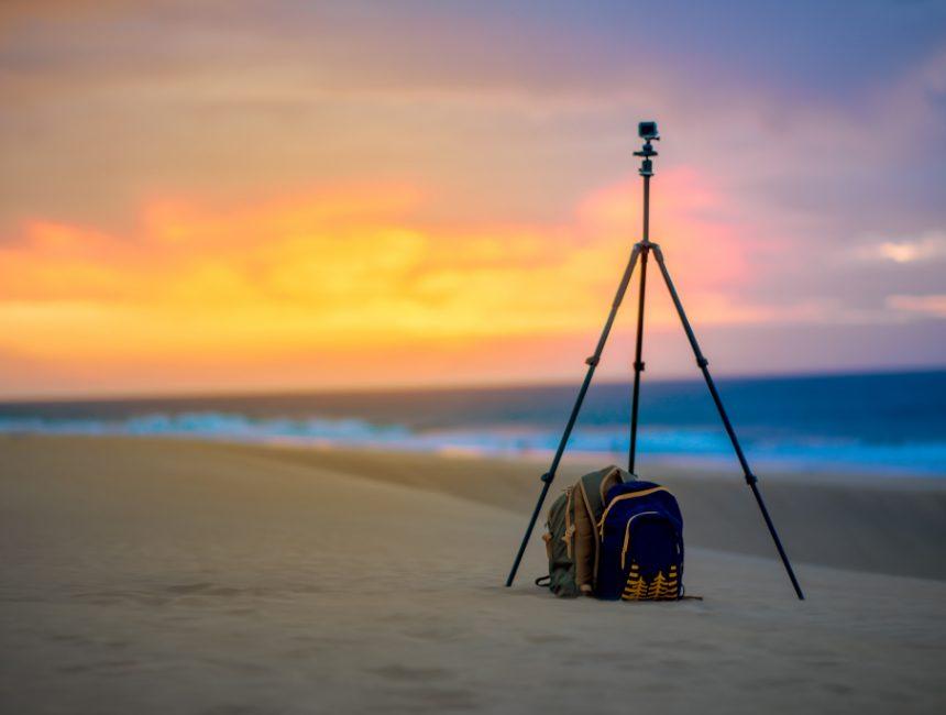 rugzak met cameravak statief zonsondergang strand